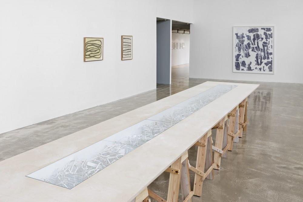 Robert Wood, WAKE, Konstruksjon av kartong på bord av finér, glass. I bakgrunnen Mette Stausland, MOVING PARTS, 2015, Blyant på papir, og READING RIVERS V, 2015, Kritt på papir/collage.